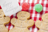 Close up shot of happy holidays tag with gingerbread candies — Stock Photo
