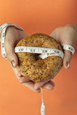 Bread with tape measure on human hand — Stock Photo