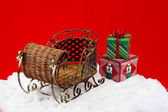 Gifts on the snow beside wicker sleigh — ストック写真