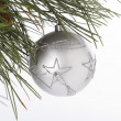 Star shape on christmas bauble hanging on christmas tree - Stock Photo