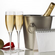 Champagne bottle flutes and ice bucket with christmas baubles — Stock Photo