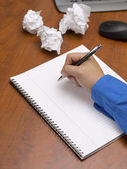 Close up shot of a person writing on spiral notepad on desk — Stock Photo
