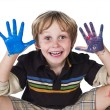 Smiling little boy with paint on his hands — Стоковая фотография