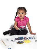 Portrait of cute girl with paint brush and paper — Stock Photo