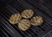 Hamburger patties cooking on grill — Stock Photo