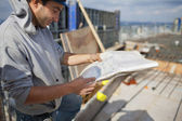 Young architect looking at blue print — Stock Photo