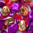 Stock Photo: Golden and purple candies arranged randomly over white