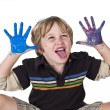 Boy with paint on his hands and sticking out tongue — Stock Photo