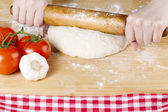 Rolling pin knead on dough — Stock Photo