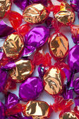 Golden and purple candies arranged randomly over white — Stock Photo