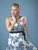 Gorgeous woman wearing a summer dress holding a flower — Stock Photo