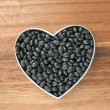 Black beans on a heart shape container — Stock Photo
