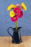A pitcher of pink and yellow daisy — Stock Photo