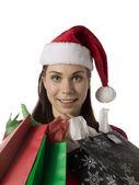 Kobieta w kapeluszu santa z papieru torby na zakupy — Zdjęcie stockowe