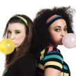 Young women standing back to back and blowing bubble gum — Stock Photo