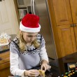 Blonde girl making gingerbread house — Stock Photo
