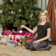 Close up of girl sitting in front of christmas tree — Stok fotoğraf