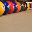 Pool balls arranged against cushion — Stock Photo #19347135