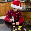 Stock Photo: Pre adolescent boy making gingerbread house