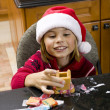 Smiling boy building gingerbread house — Stock Photo
