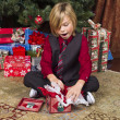 Surprised pre adolescent boy unwrapping his christmas present — Stock Photo