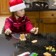 Stock Photo: Thoughtful boy looking away while making gingerbread house