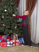 Blonďák dotýkají vánoční strom — Stock fotografie