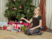 Close up of girl sitting in front of christmas tree — Foto Stock