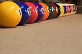Pool balls arranged against cushion — Stock Photo