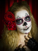 Portrait of a ugly woman with face paint and red roses in hair — Stock Photo