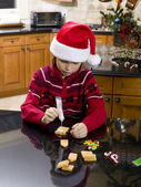 Pre adolescent boy making gingerbread house — Stock Photo