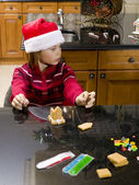 Thoughtful boy looking away while making gingerbread house — Stock Photo