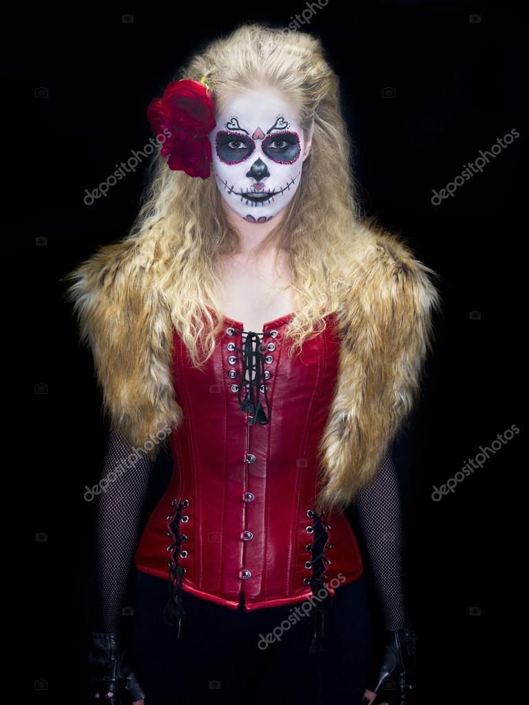 Portrait shot of a scary girl wearing traditional sugar skull make-up against black background — Stock Photo #19347151