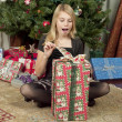 View of a girl with open mouth opening a gift box — Stock Photo #19350119