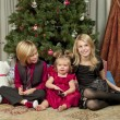 Stock Photo: Image of brother and sister with a cute baby girl sitting on floor with Christmas tree