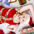 Woman lying on floor with christmas gifts on the side - Foto Stock