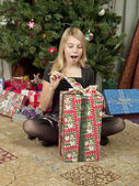 View of a girl with open mouth opening a gift box — Stock Photo