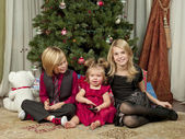 Image of brother and sister with a cute baby girl sitting on floor with Christmas tree — Foto Stock