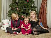 Imagem de irmão e irmã, com uma bonita menina sentada no chão com a árvore de natal — Foto Stock