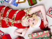 Woman lying on floor with christmas gifts on the side — Foto de Stock