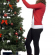 Beautiful young woman in santa hat decorating christmas tree — Foto de Stock