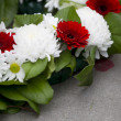 Close up shot of flowers arranged at war memorial - Stock Photo