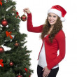 Beautiful girl smiling while putting a christmas ball in christm — Stock Photo