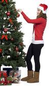 Beautiful young woman in santa hat decorating christmas tree — Stockfoto