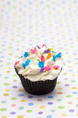 Close up shot of a cupcake with colorful sprinkles — Stock Photo