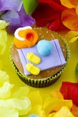 Close up top view of cupcake with decorative toppings surrounded — Stock Photo