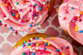 Extreme close up shot of a strawberry cupcake with tons of sprin — Stock Photo