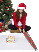 Girl sitting while starting to wrap a gift — Stock Photo