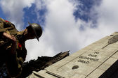 Low angle view of a soldier in hat standing by war monument — Stock Photo