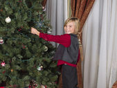 Portrait of a boy touching christmas tree — Stock Photo